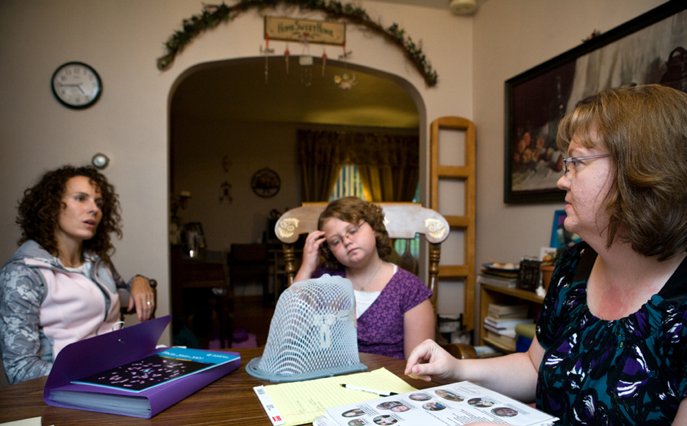 Ali Borgen, center, looks at a radiation mask that she wore during her treatments for cancer while her mom, Karen Borgen, right, and Kristen Abner compare notes on a possible cancer cluster in the area.