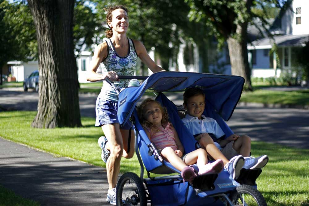 Kristen Abner prepares for a marathon for the Leukemia and Lymphoma Society by running with her two children, George, 5, and Hannah, 3 1/2, on Belmont Road in Grand Forks.